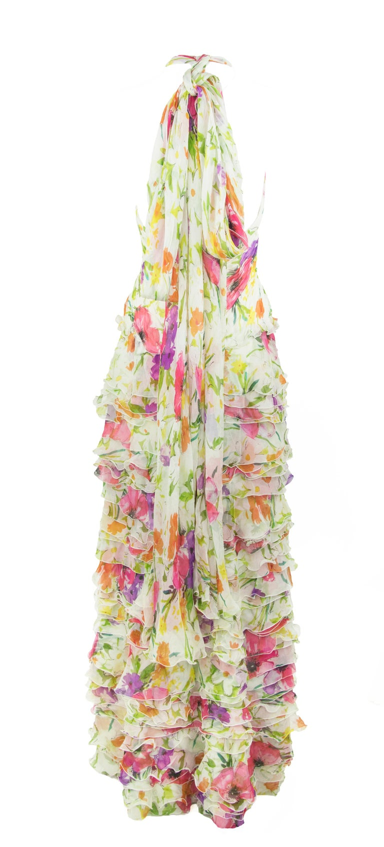 Incredible layers of white floral printed chiffon ruffles and a gathered bodice make this gown elegant and feminine.  Perfect for a summer soiree.  A halter neck with along tie gives this gown a dramatic effect.  Size: 2  Condition: In pristine