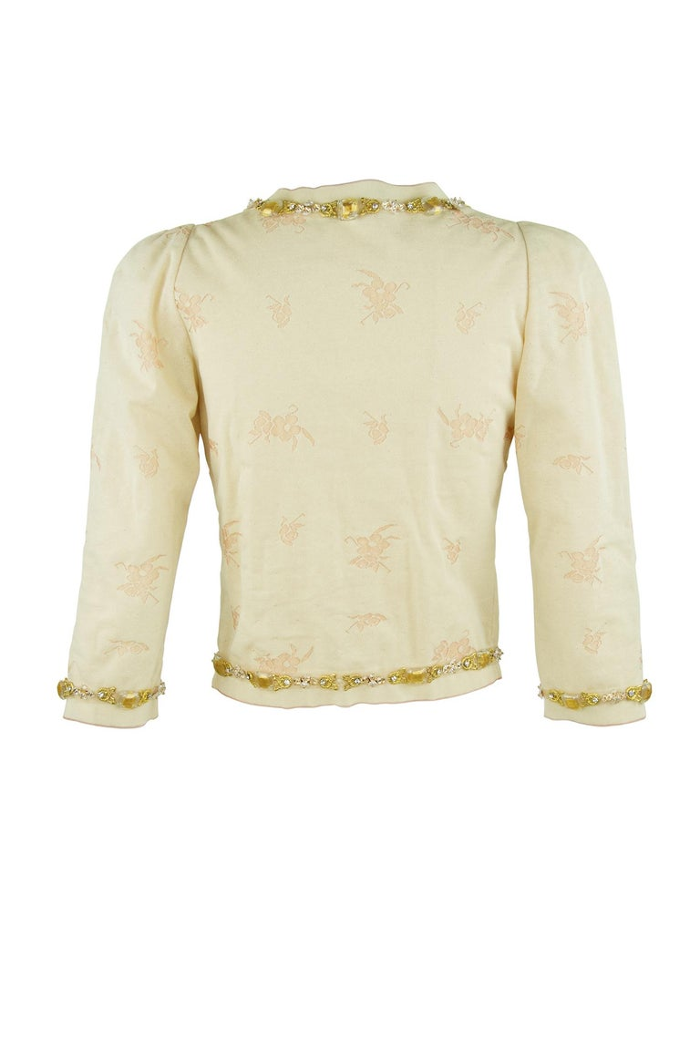 Stunning  light peach jacquard knit cardigan with floral detail.  A gold embellished boarder adorns this sweater and makes it the perfect compliment to a beautiful pair of dress pants or skirt.  Would also look great styled with jeans.    Size: FR