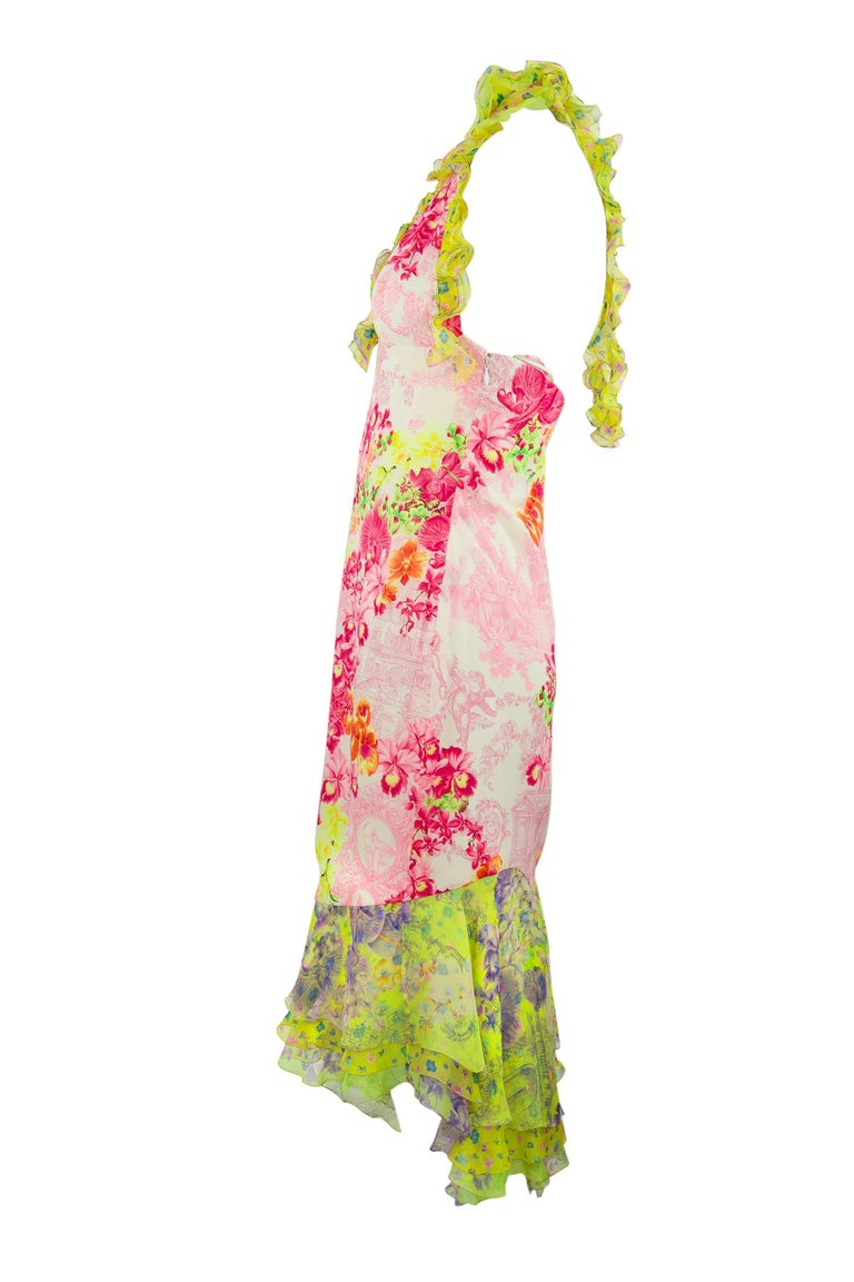 Gorgeous bright colors adorn this floral print dress, a rare and collectible Versace piece.  The body fabric is made of light and bright pink floral print.  With a bright green and yellow contrasting fabric on the flounce of the skirt ruffled halter