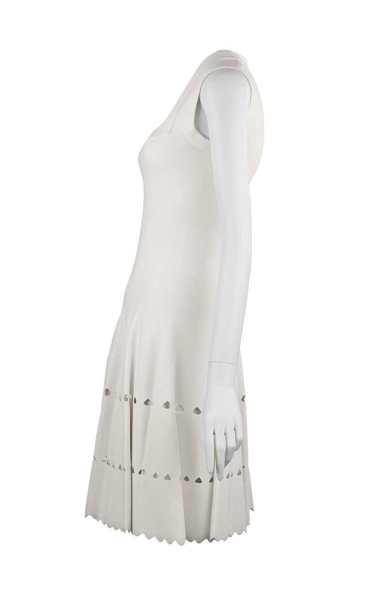 Gorgeous white Alaia fit and flare dress in a stunning knit fabric that has laser cut detail along the skirt.  Features a square neckline with a delicate scalloped finish on the edges.   Size: FR 36  Condition: New with tags  Composition: 85%