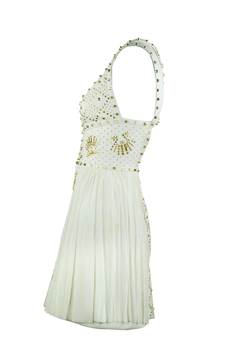 Iconic Gianni Versace piece composed of white leather trim, chiffon and gold studs.  Intricate design work with incredible motifs composed of gold studs.  White Chiffon skirt.  Rare and collectible Versace dress.  Size: IT 38  Condition: Very good