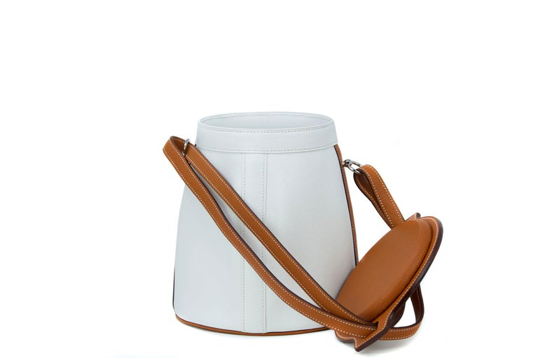 This Hermes farming bag is a truly rare collectors item.  Crisp white epsom leather with the coveted Hermes Barenia leather.  Features adjustable leather strap and palladium hardware.   Condition: New  Measurements: Diameter Top 14cm / 5.5