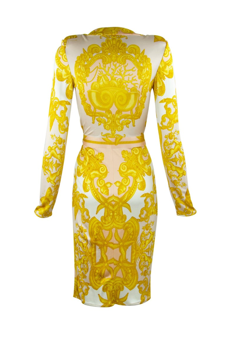 Iconic wrap dress made of sexy silk jersey, featuring a v neckline and long sleeves.  This Versace print is hard to miss, composed of gorgeous white, gold and light pink.  Signature medallion belt.  Size: IT 42 (the last picture shows size IT 40, as