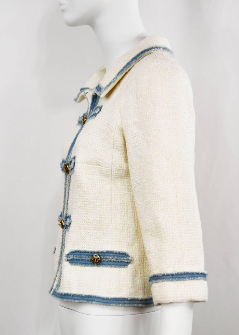 Chanel runway, very rare, elegant white Cotton Boucle Jacket with light denim trimmed frayed detail, FR 36, US 4.  Classic chunky gilt 'CC' buttons down the front.  There are two pockets.  It is lined in silk and the hem is chain weighed.  This item