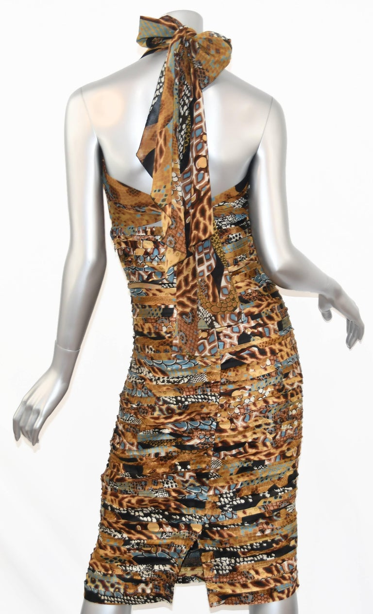 This Versace dress from the Runway has a sexy halter neckline that ties in a bow with a peek-a-boo cut out and open back.  Horizontal bias fabric strips sewn down the bodice ensure an alluring fit.  This sensational gown in colors of browns and