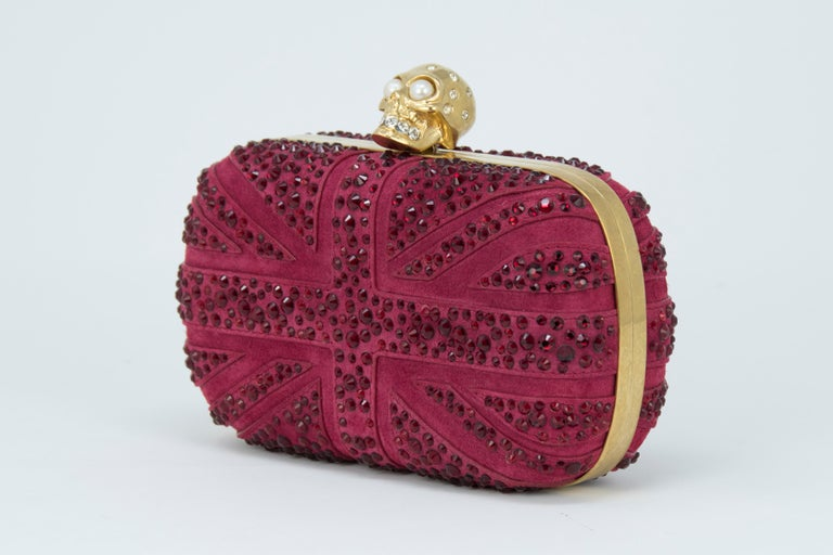 Alexander McQueen Britannia Skull Box Clutch in dark red suede Union Jack flag inspired design with signature gold skull hardware with rhinestone and pearl embellishments.  Condition: New condition  Dimensions (Approximate): 3.9