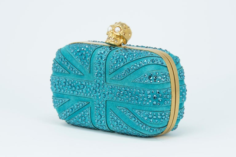 Alexander McQueen Britannia Skull Box Clutch in blue suede Union Jack flag inspired design with signature gold skull hardware with rhinestone and pearl embellishments.  Condition: New condition  Dimensions (Approximate): 3.9