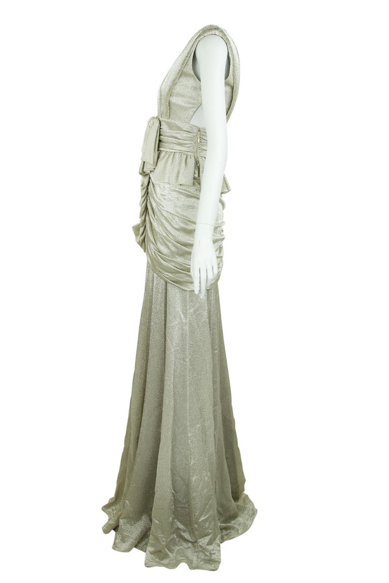 Incredible detail on this silver gown by dutch designer Viktor & Rolf.  Features gathering around the hips with a bow right below the bust.  This dress is breathtaking and will look beautiful at a formal black tie event.  Size: IT 40  Condition: