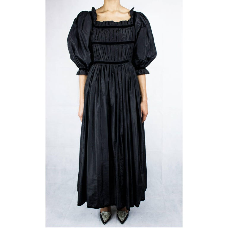 This beautiful black taffeta evening gown, circa 1970 although quiet in style evokes timeless elegance. Every details is designed to celebrate unapologetic femininity. Constructed from opulent taffeta material. The gathered skirt is ample and