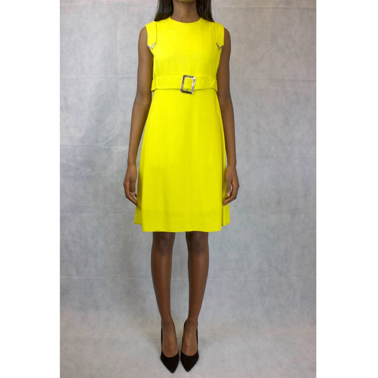 This vibrant Ted Lapidus couture-finished dress No: 21853 is a French take on the fashion that characterised London Mod subculture of the 1960s.  An A-line shift dress made from linen in the flamboyant yellow of the era. The metal buckle on the