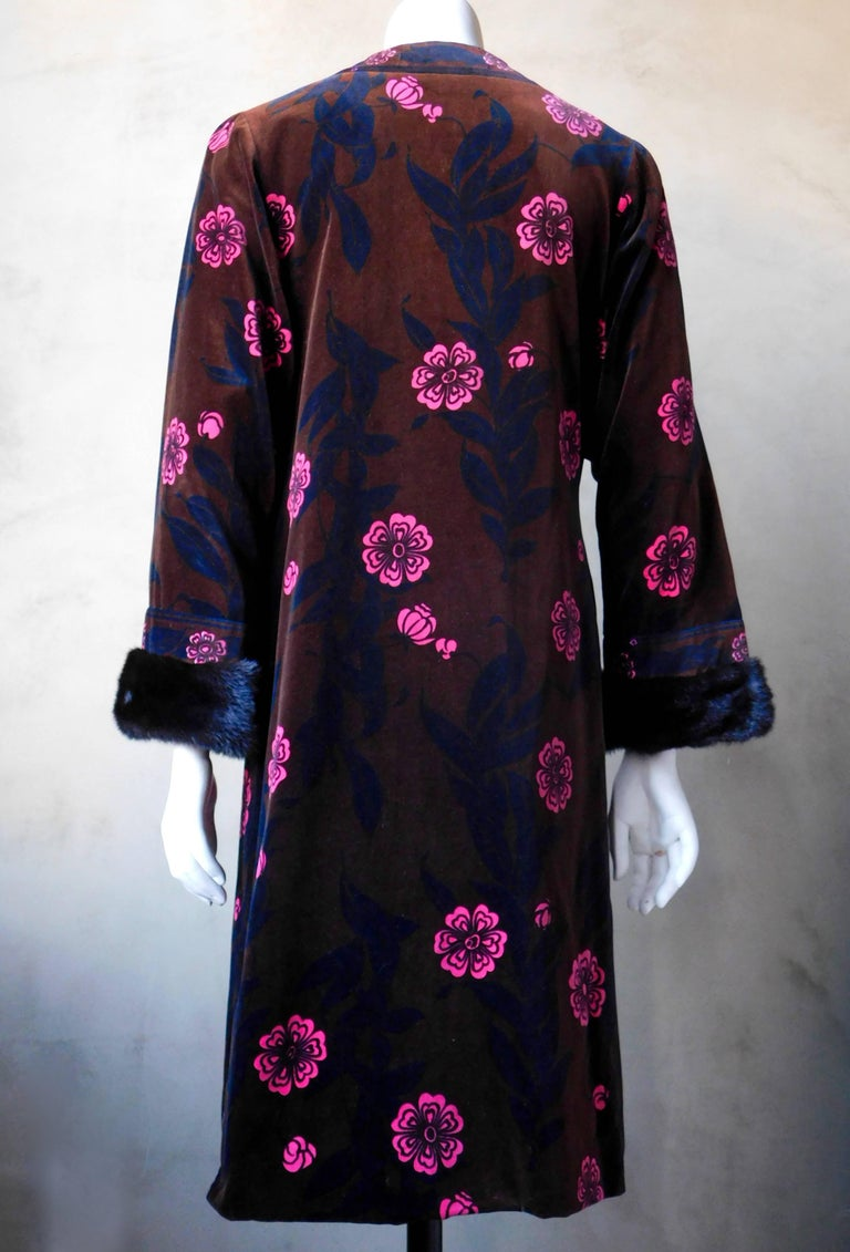 A very rare late 1960's Emilio Pucci printed velvet coat with mink cuffs. Chic climbing vine print in subdued black and brown with hot pink flowers. The coat has side slits and covered buttons.  In very good condition and ready to wear! sleeve