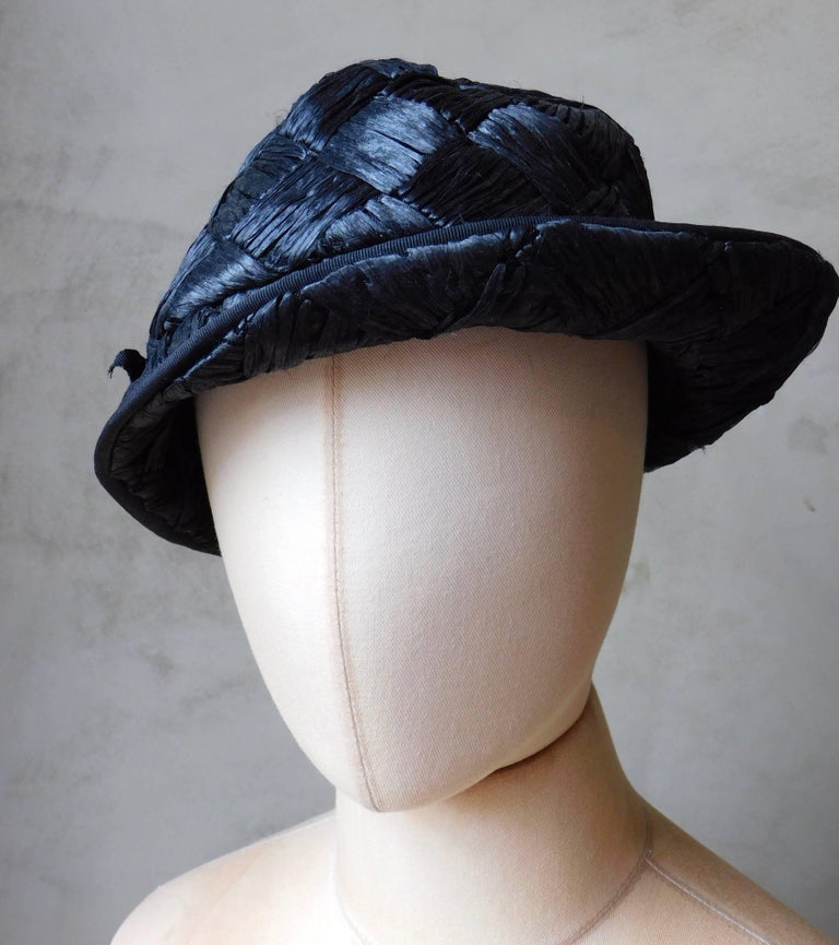 Very chic French 1940's woven straw hat in an asymmetrical design. Woven from black raffia  and trimmed with black grosgrain ribbon . Fits a regular size head  size 56cm(22