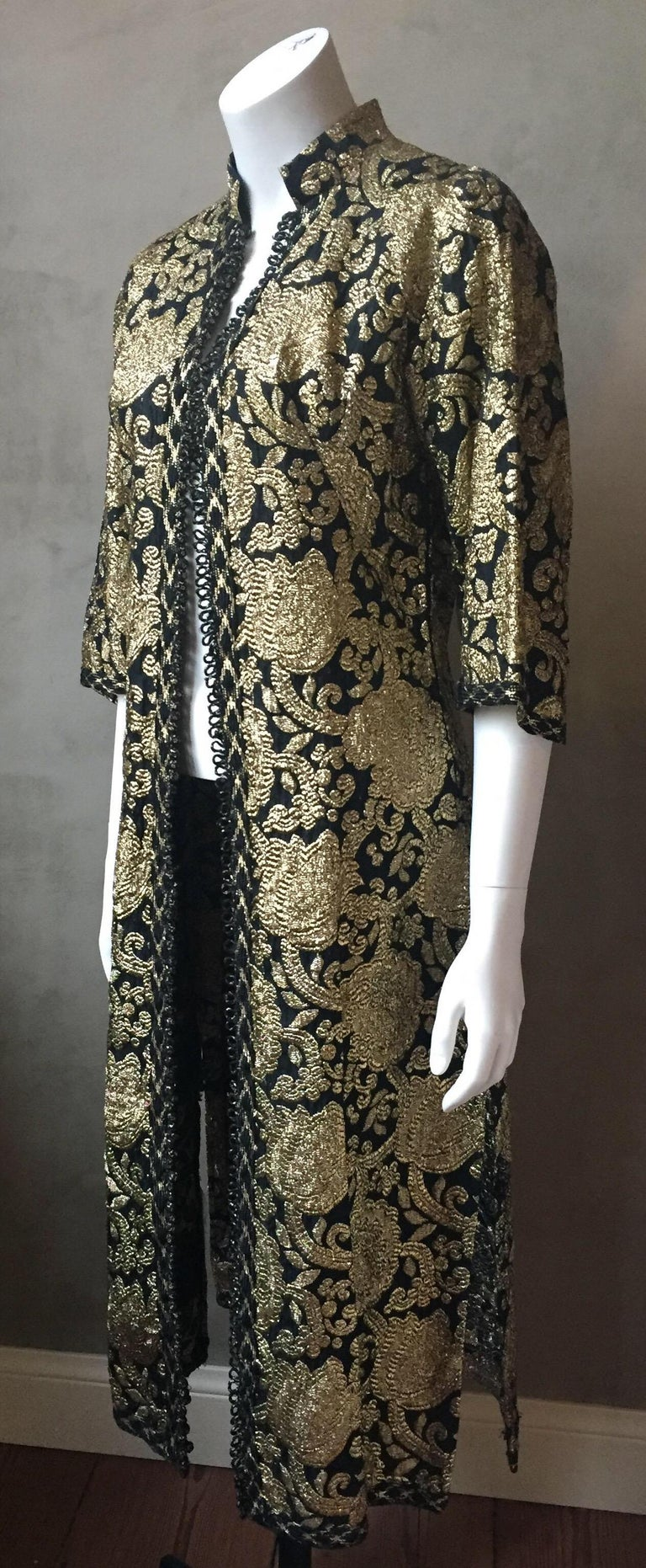 A vintage Turkish style gold and black brocade dress or evening jacket. Tiny knot buttons all the way down the front and a side zipper allow the dress to be worn completely closed when worn as a dress, or button the top half and leave from waist