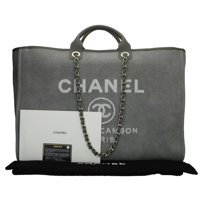 Authentic CHANEL Deauville Tote XL Grey Canvas with Silver Hardware 2015.  This bag is in a pristine condition.  Exterior Condition: Pristine condition, corners show no signs of wear, outside of the bag shows no signs of wear.  Interior Condition:
