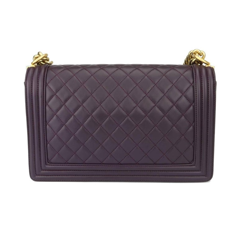 Authentic Chanel New Medium Boy Dark Purple Lambskin with Brushed Gold Hardware 2016.  This stunning bag is still in a pristine-brand new condition, the bag has never been worn and all blue plastic protectors still on.  Exterior Condition: Pristine