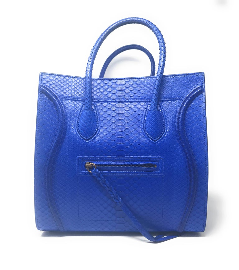 Celine Phantom in gorgeous and intense Blue Python skin, features the distinctive wings, sturdy handles, and braided zipper pull. This is the medium size which can be compacted by folding the wings inward. It has an exterior and an interior zippered