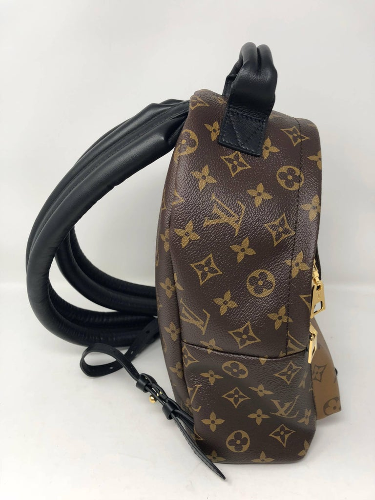 Louis Vuitton Reverse Palm Springs Backpack PM in new condition. The back pack handles are made of a strong black cowhide and are wide for easy comfort. They are also adjustable for any height. Unique reverse monogram covers the front pocket and the