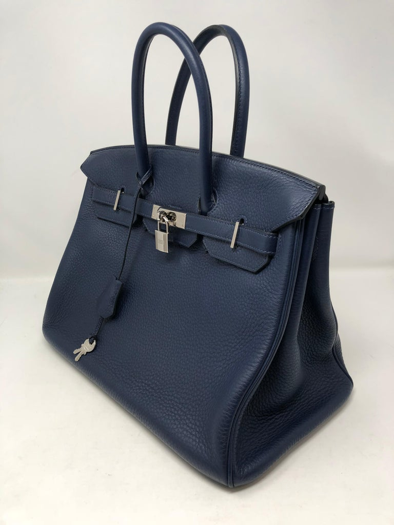 Hermes Birkin 35 Bleu Abysse with palladium hardware. This beautiful sapphire/ navy blue is more stunning in person. Mint condition with plastic still on front hardware. The Birkin is Clemence leather which holds up very well. Highly coveted color