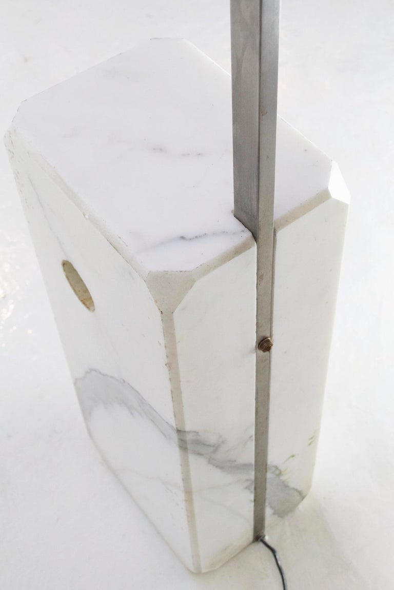 This is an original iconic Arco lamp. This particular one was produced in the 1970s this is in very good used condition. The Carrara marble slab also has character with a distinct grey line contrasting the white.  This is a modern overhead lamp