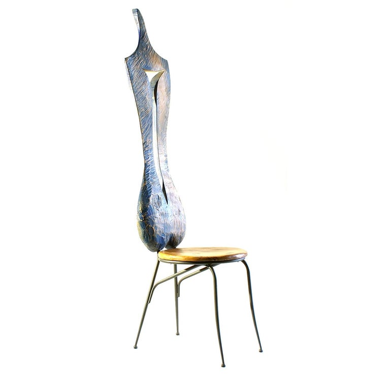 Paying homage to the sensual curves of the female body, the sculptural backrest of this unique chair is entirely crafted by hand of maple wood with a sinuous hollow space in the center that adds a dynamic movement and a light blue whitewash finish.