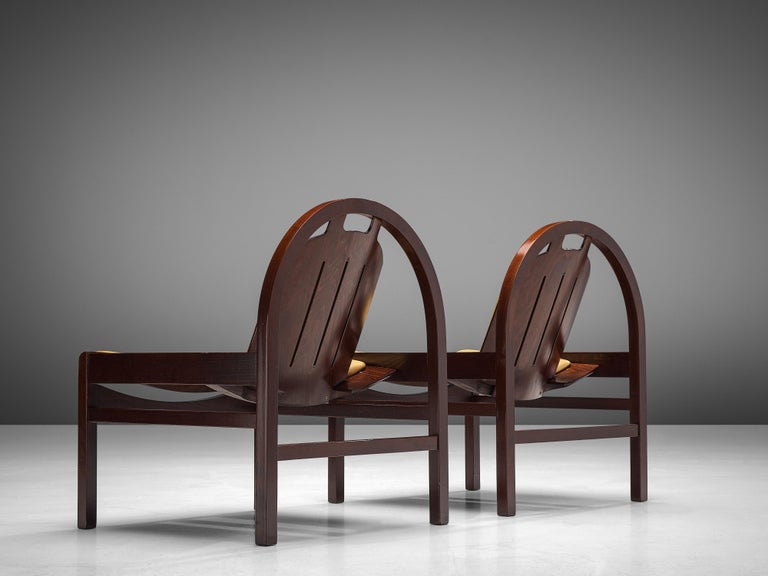 Baumann, 'Argos' easy chairs, stained beech, leather, France, 1970s  These 'Argos' lounge chairs are manufactured by Baumann in France in the 1970s. The chairs feature a round frame that supports the tilted backrest. The tilted seat is wide and low