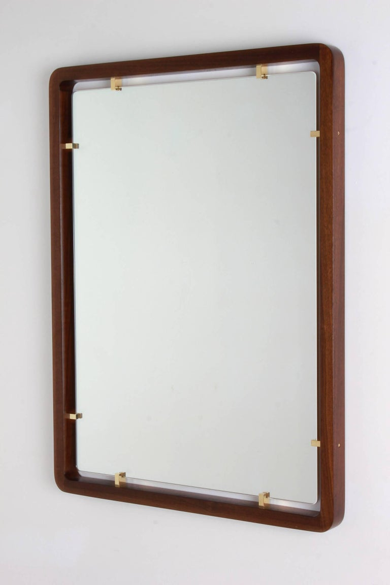 Beautiful floating mirror with walnut frame and solid brass fittings.