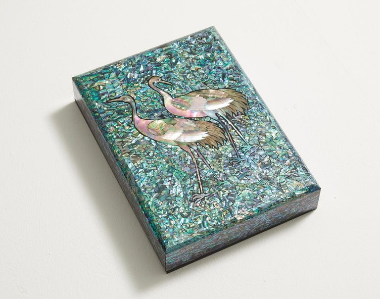 This artwork presents a wooden box inlaid with the image of cranes carved from mother of pearl. The sky is engraved with the blue shade of mother of pearl to highlight the profound mysteriousness of the cranes. The brilliant light shines gloriously
