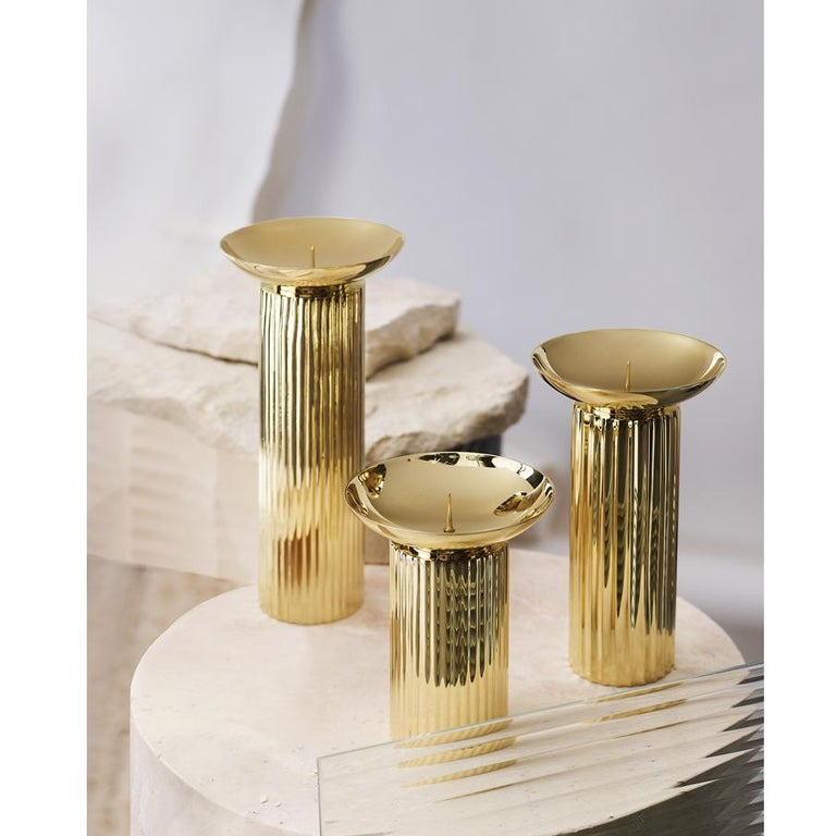 Introducing the Aristotle collection of handmade brass candle holders. Bold, gleaming brass columns, these pieces are offered in three sizes. Large and small candle holders feature a gentle ribbed vertical patterning whilst the medium size subtly