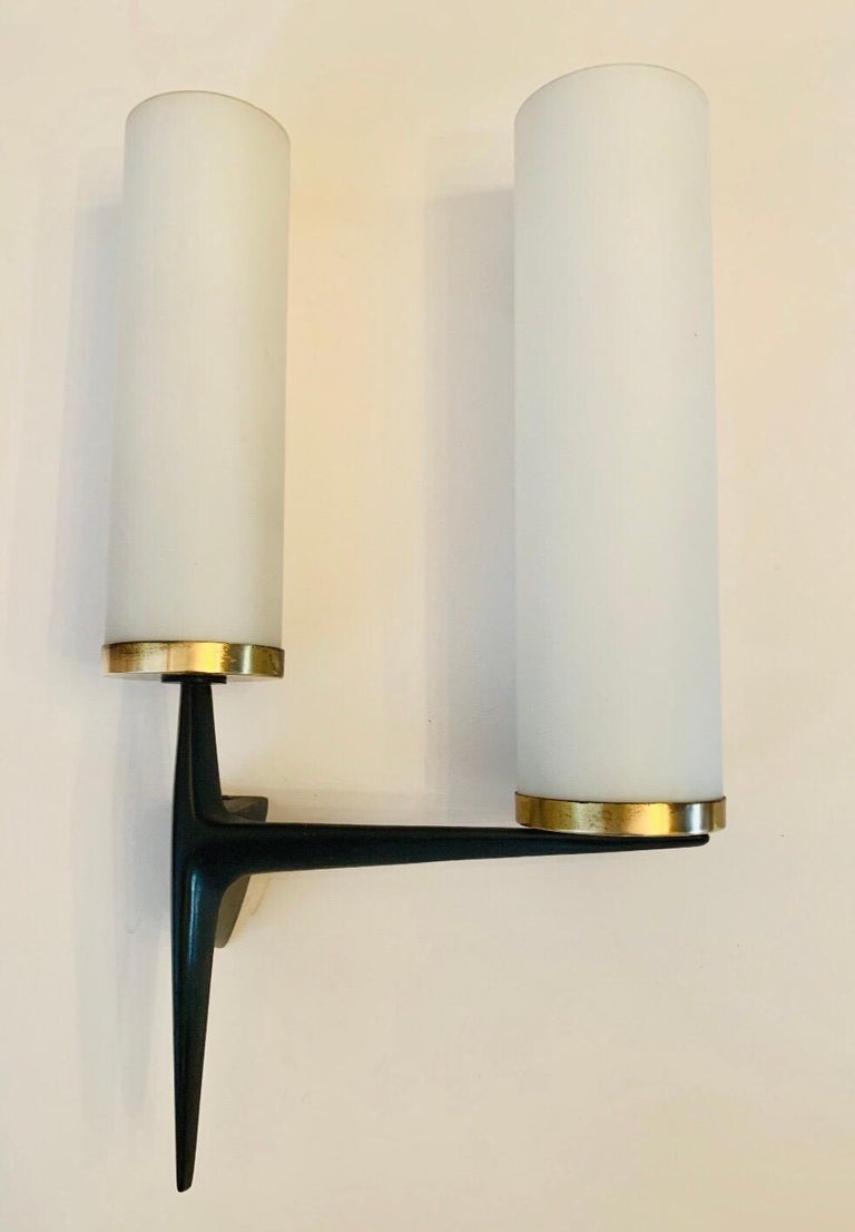 A wonderful French 1950s black matte enamel iron wall lights with white matte glass cylinder shades by Arlus. Newly rewired