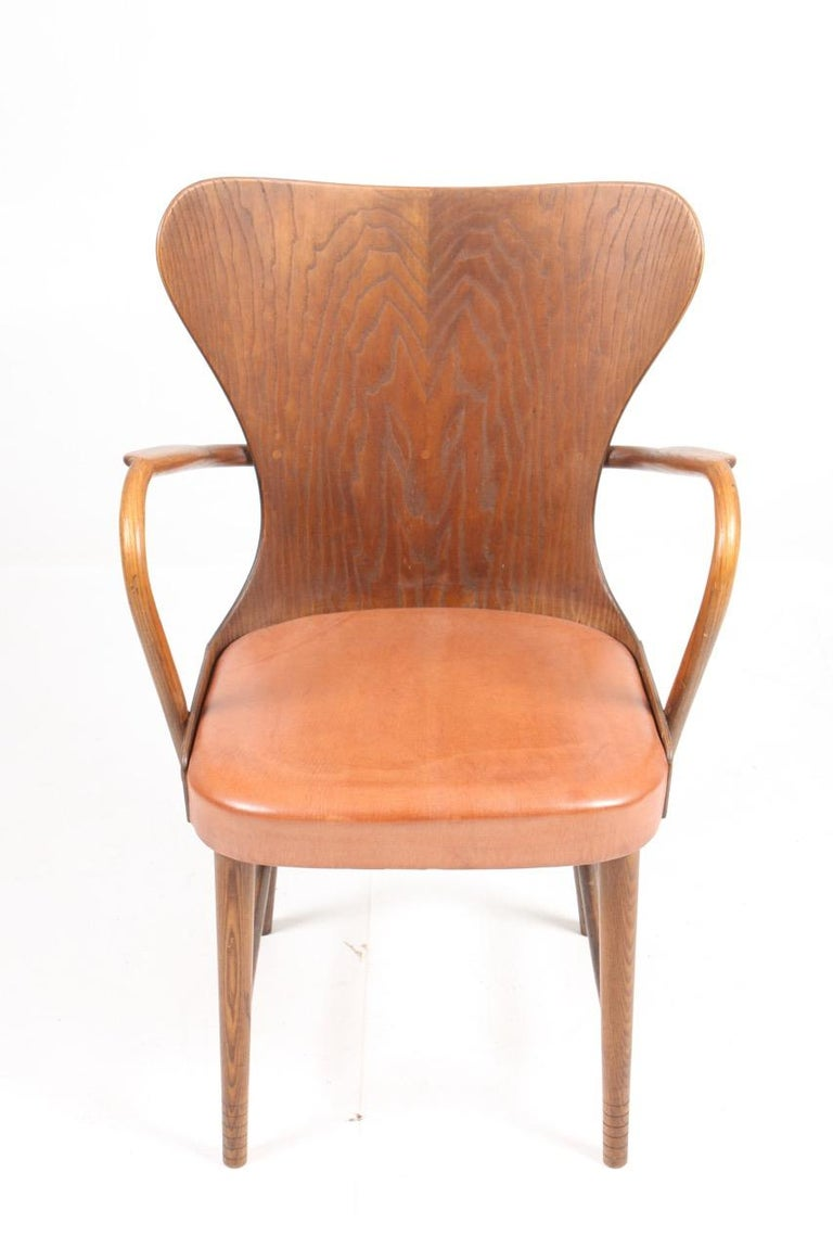 Armchair in oak and patinated leather designed and made by Fritz Hansen cabinetmakers in 1940s. Made in Denmark. Great condition.