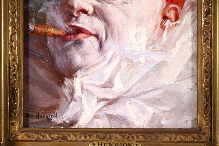 A charming oil on panel circa 1900 by French impressionist painter Armand Francois Henrion depicting a portrait of a Pierrot - a French clown - wearing white ruffles and a red hat and smoking a cigar.   Signature: Signed lower