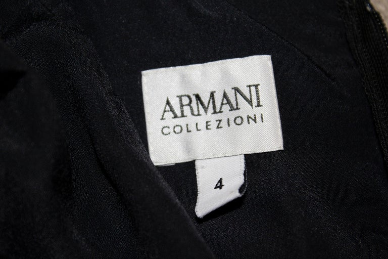 A chic black cocktail dress by Armani Collezzioni, The dress has a pleated skirt area and bust with stitching and deicoration around the neckline.  Size 4  Bust 34'', waist 29'' length 41''