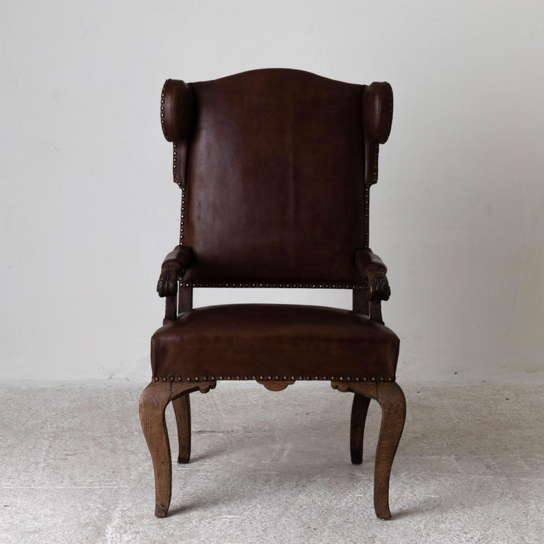 """Chair French Wingback Rococo Period France. A wingback chair made during the Rococo period in France 1720-1750. Original finish and upholstered in a waxed brown leather.   Measures: H: 47.8  W: 25""""  D: 23.5""""   SH: 20""""."""