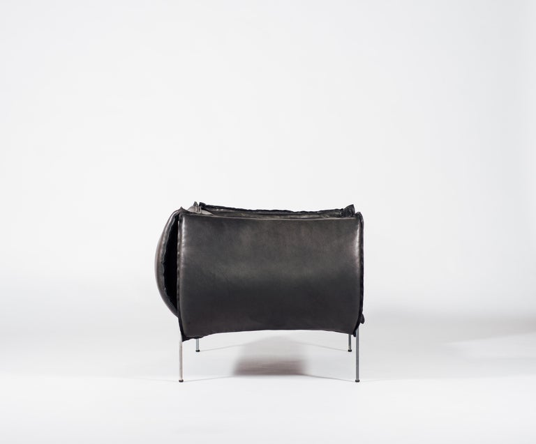 Bulging over its edges, this contemporary single sofa seat by Klein Agency screams comfort. Puffy cushions hug the laser cut steel frame, creating a supple cocoon, demanding you to wallow in its softness. With its bulky front and bulging back, the