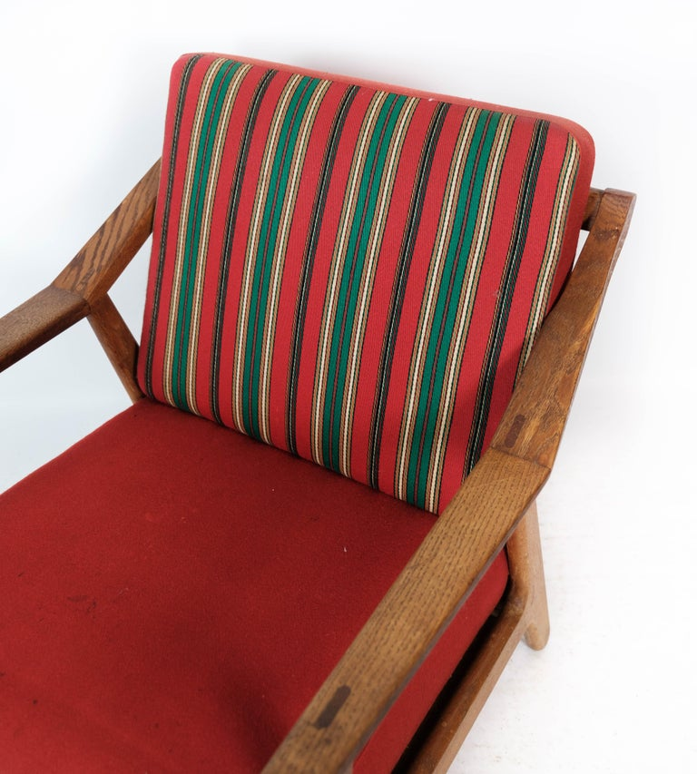 Armchair in oak and upholstered with red fabric, designed by H. Brockmann Petersen in the 1960s. The chair is in great vintage condition.