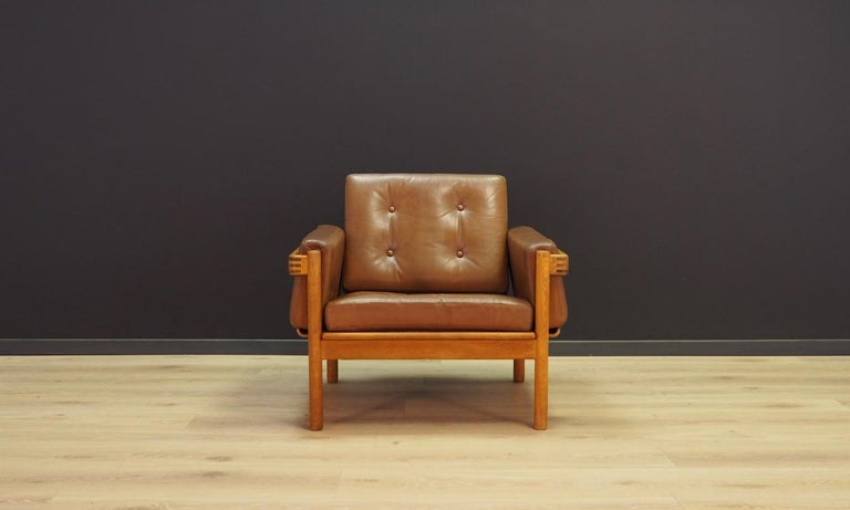 Unique armchair from the 1960s-1970s, a beautiful Minimalist form, Scandinavian design. Armchair covered with original leather (color - brown), construction made of oak wood. Preserved in good condition (scratches and bruises on the skin), directly