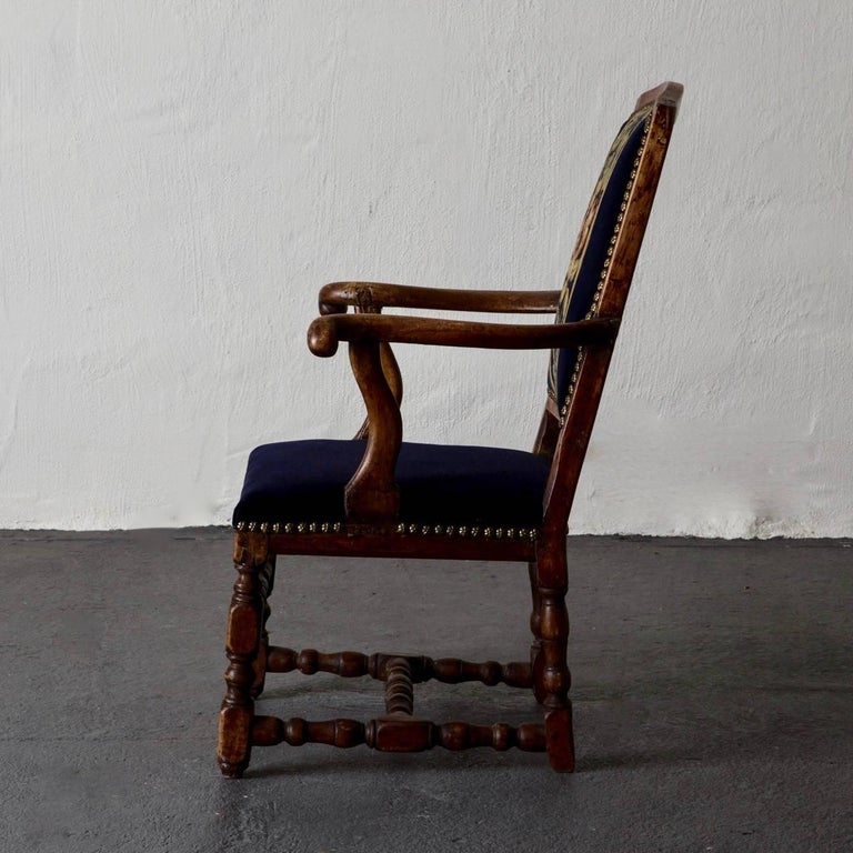 Armchair Swedish Baroque oak, Sweden. A single armchair made in Sweden during the early part of the Baroque period. Frame made of oak with an upholstered back splat and seat in dark blue. Out-curved armrests and turned legs with a foot cross.