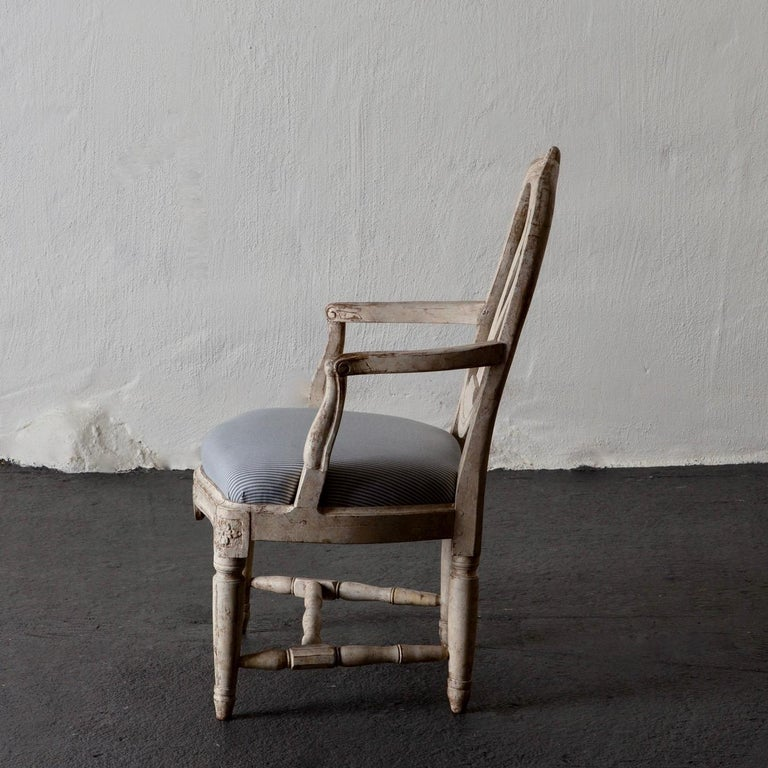 Armchair Swedish Gustavian 1775-1790 white washed, Sweden. An armchair made during the early part of the Gustavian period circa 1775-1790. A rounded open back splat with an urn shaped middle part decorated with a carved rose on top. Curved armrests