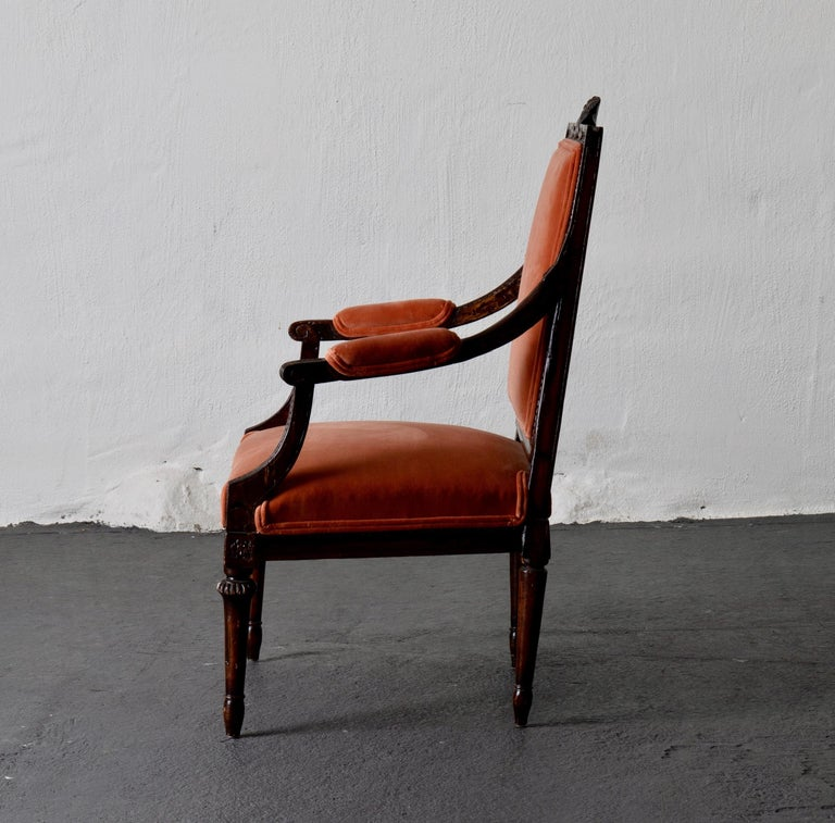 "Armchair Swedish Gustavian dark apricot velvet, Sweden. An armchair made in Sweden during the Gustavian period (1790-1810). Carvings on backrest and frieze in the shape of a so called ""humle flower"