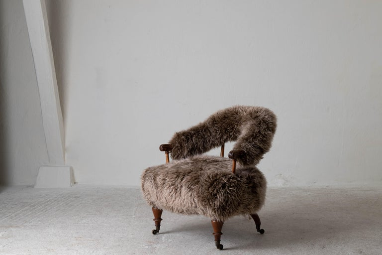 Armchair Swedish late 19th century fur beige brown Sweden. An armchair made during the later part of the 19th century in Sweden. Reupholstered in a light brown long haired fur. Frame in mahogany and legs ending in brass casters.