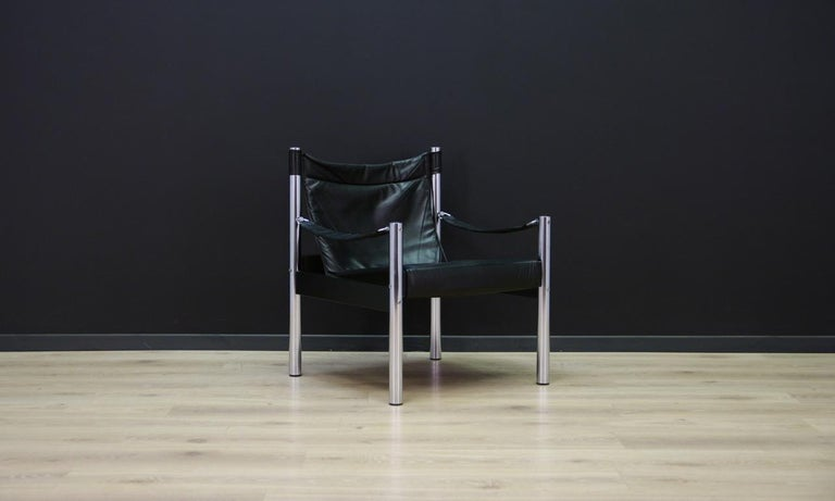 Stylish armchair from the 1960s-1970s, a beautiful minimalistic Danish design. Armchair covered with original leather (color - black). The construction is made of chromed metal. Preserved in good condition (visible scratches on the skin, minor