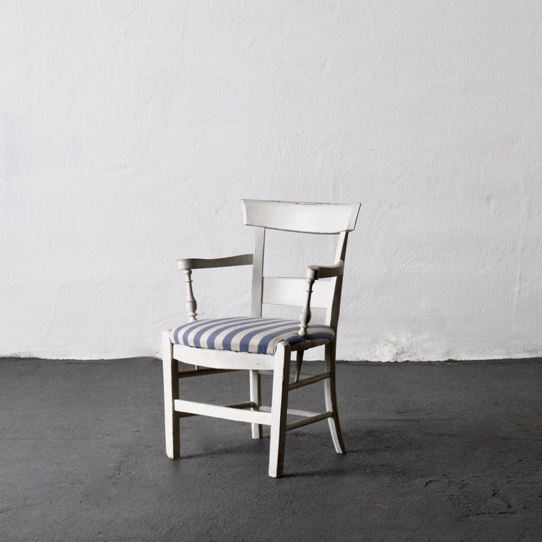 Armchair white French 19th century blue and white upholstery, France. An armchair made in a fruit wood during the 19th century in France. Restored paint and upholstered seat in a blue and white striped cotton fabric.