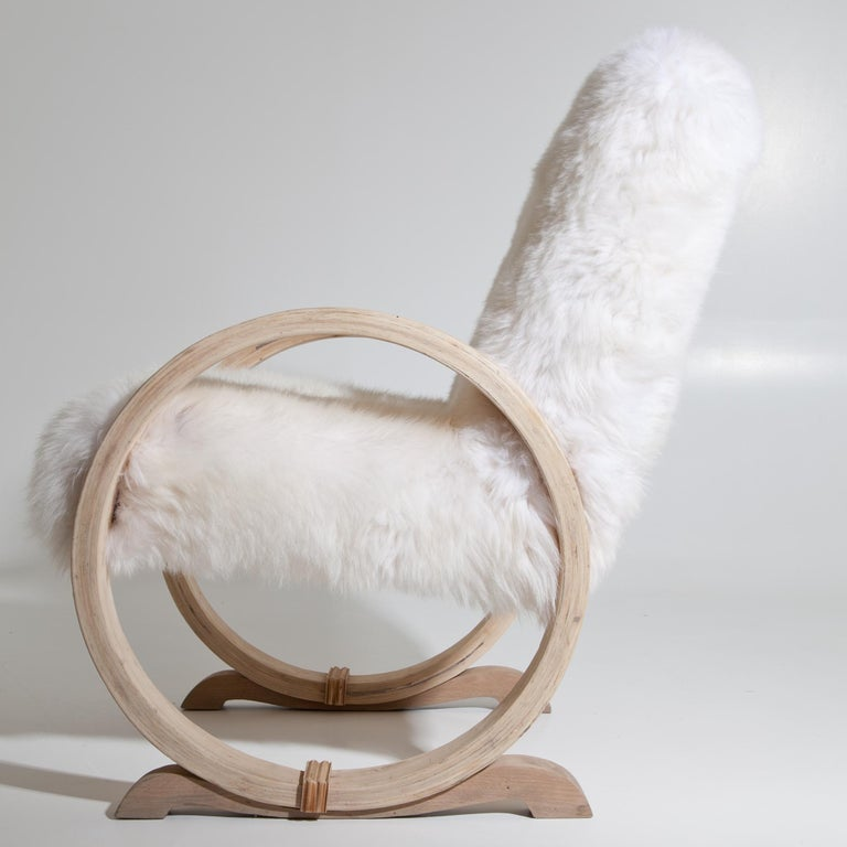 Armchair standing on hoops that serve as armrests. Seat and backrest were reupholstered with a white sheepskin.