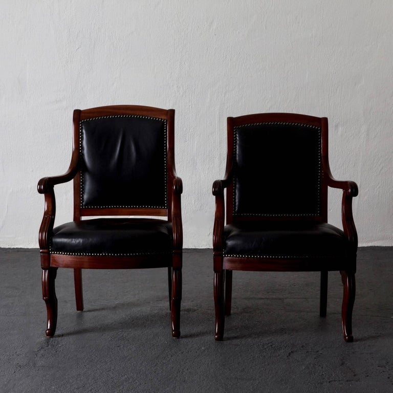An assembled pair of French Empire armchairs made in mahogany and upholstered in a soft black leather decorated with nailheads. The chairs both comfortable and stylish.