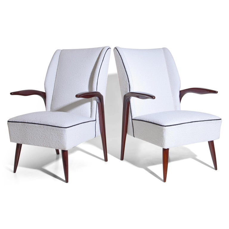 Pair of armchairs on conical legs with slightly curved armrests. Seat and backrest were reupholstered with a high quality white bouclé fabric with black piping.