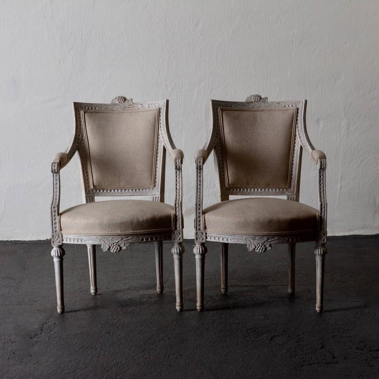 Armchairs pair of Gustavian 19th century Swedish white Sweden. A pair of armchairs made during the Gustavian period in Sweden. Frame in white washed finished with nail tip carvings and flowers. Legs are rounded and channelled. Seat, back and