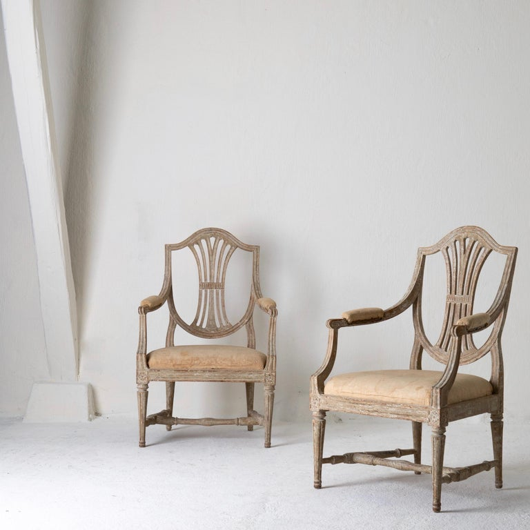 A pair of armchairs made during the Gustavian period in Sweden 1790-1810. Stripped to their original greenish gray finish. Beautiful carvings.
