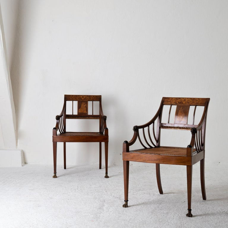 Armchairs pair of Swedish light mahogany, early 19th century, Sweden. A pair of armchairs made during the early 19th century in Sweden. Made from mahogany with a seat of rattan. Details such as lions head and feet along with inlays in lighter wood.