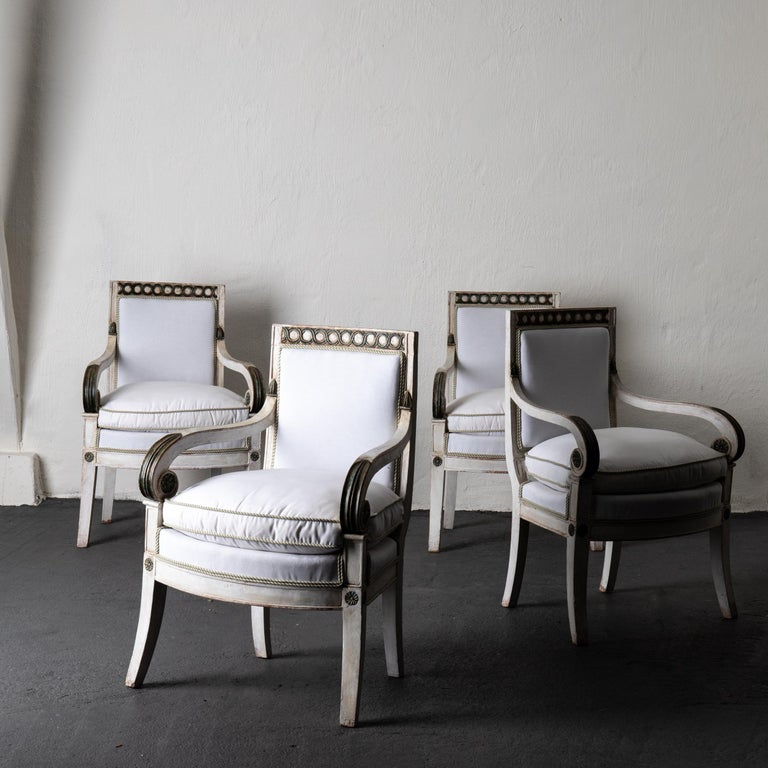 Armchairs set of 4 French white green Empire chairs France . A set of 4 armchairs made during the Empire period. Painted in a distressed white with dark green details. Upholstery in a white fabric with green and white piping. Carved armrests with