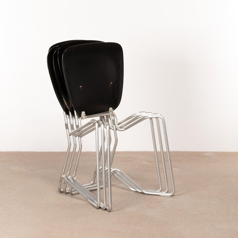 Armin Wirth folding / stacking chair for Aluflex Switzerland designed in 1951. Early production with a smart constructed lightweight frame of aluminum and black dyed plywood seats all in good original condition with traces of use.